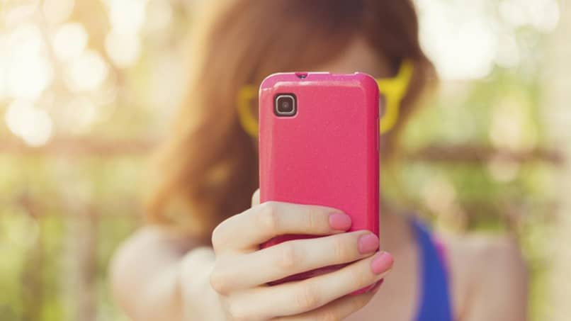 woman uses pink phone